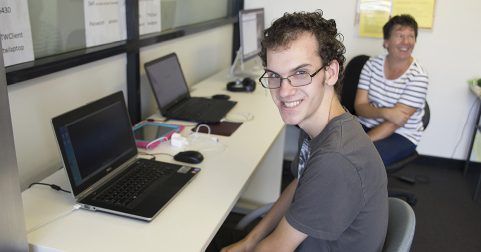 Raymond Clough sitting at a computer smiling while taking part in disability service provider Northcott's Life Skills program