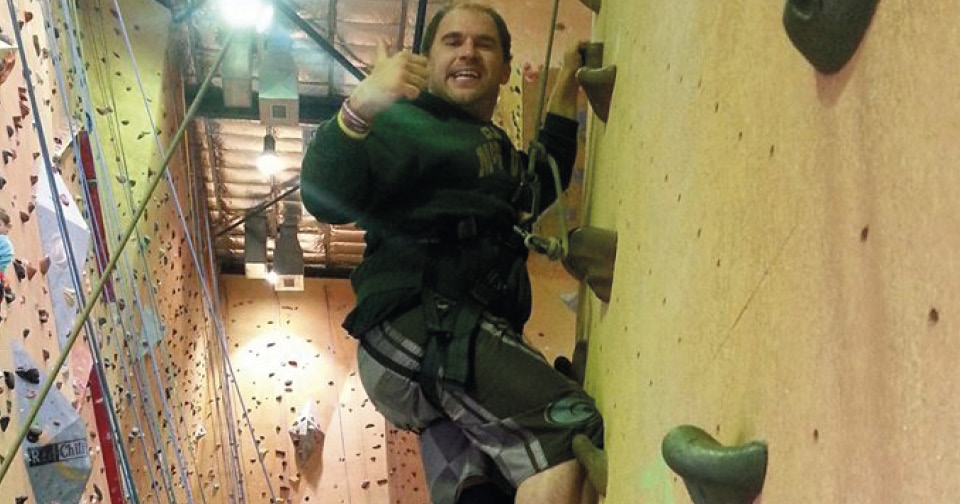 Tony Petrin climbing up a wall with rocks on it indoors