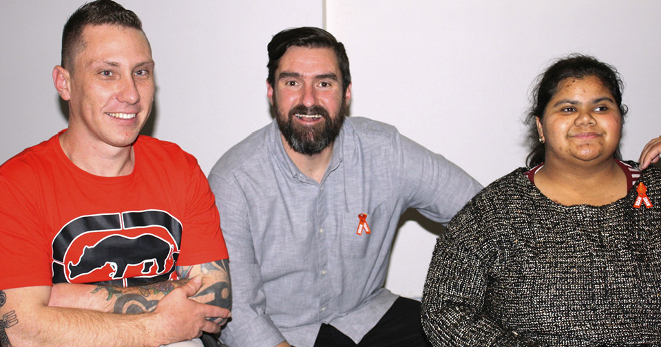 Comedian Andrew Bennett with two people enjoying themselves at Northcott's Spina Bifida Awareness Week comedy event